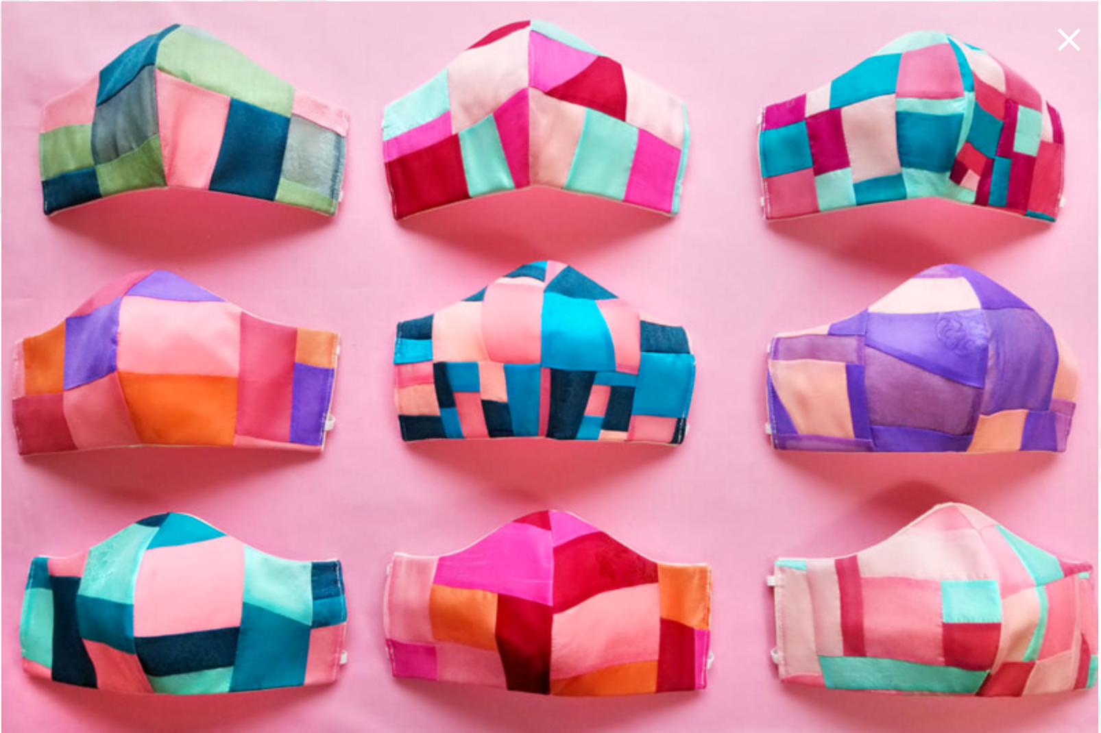 A three by three grid of nine masksk, each a colorful patchwork of fabrics, set on abright pink background.