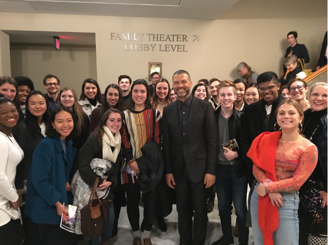 """Group of students and professors standing inside with a sign in the background that reads """"Family Theatre, Lobby level"""""""