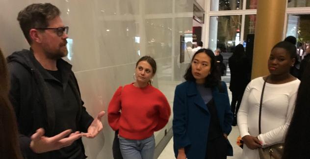 Professor Ian Bourland talks to a group of three students inside an atrium.